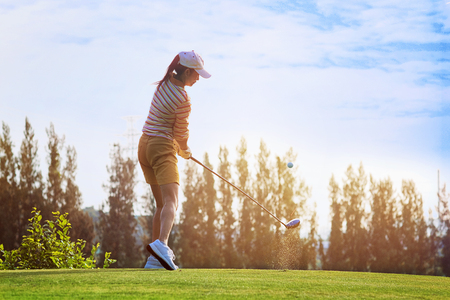 Fluffing of golf ball and tee flying away from the teeing ground impact by the woman golfer player after swing plane of proper stance addressing the ball