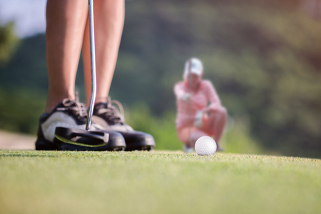 Golf ball being hit impact by the putt of player on the green with golfmate in attention checking putting line in background Stock Photo
