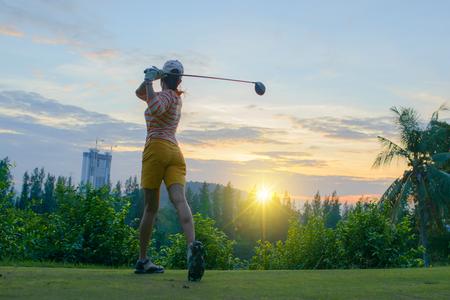 Joueur de golf femme en action de fin de downswing du pilote de bois, après avoir frappé la balle de golf loin du départ au fairway à venir, paysage coucher de soleil en arrière-plan Banque d'images - 92071757