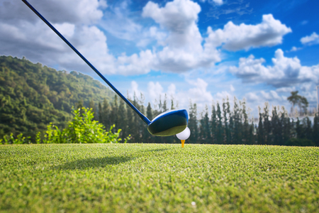 wood driver in proper address of the woman golf player on tee off at golf club, ready to hit and impact away to the fairway ahead Stock Photo