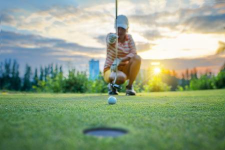 Golfbal in lijn meten en cululeren voor het beste resultaat door golfspeler op de achtergrond, bal op het groen van de golfbaan met vroeg licht van zonsondergang op de achtergrond