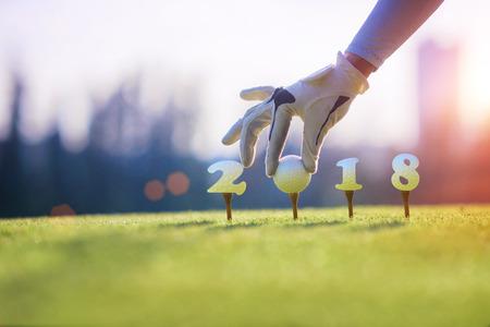 ゴルフボール招待のコンセプトは2018年、ティーオフでゴルフコースで女性の手で準備