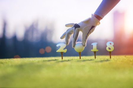 concept of golf ball invitation incomming year 2018, on the tee off prepare by hand of woman in the golf course Archivio Fotografico