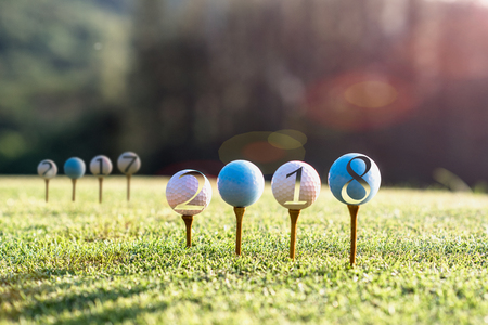 golf ball set for concept of incomming year 2018 left behind year 2017 on the tee off of the golf course