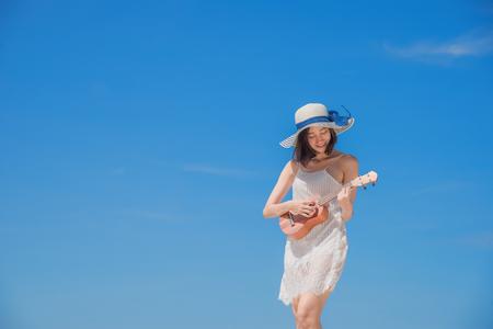 Die nette junge Frau, die Akulele auf dem Seestrand mit glücklichem lächeln auf dem Gesicht am sonnigen, gelöschten blauen Himmel des Tages spielt