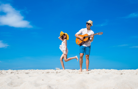 a happy and enjoy the trip honeymoon of couple lover on the sea beach by playing song music and jumping dance together at cleared blue sky daylight in background 스톡 콘텐츠