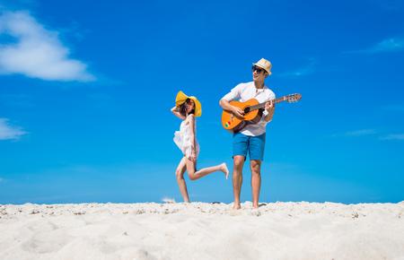 een gelukkig en geniet van de reis huwelijksreis van paar minnaar op het strand door het spelen van liedmuziek en springende dans samen bij heldere blauwe hemel daglicht op de achtergrond Stockfoto