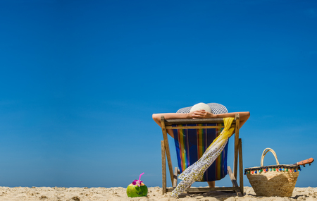 woman enjoy in comfortable life by laying on deck chair sunbath at the sea beach with fresh coconut drinking freshy, sunny brightday cleared blue sky in background Фото со стока