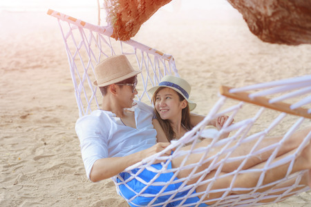 couple lover in romantic on the hammock hang on the tree at the sea beach, enjoy and happy on honey moon vacation