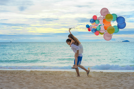 couple lover enjoy and happy on the beach playing together with running holding colorful balloons, romantic at seaside