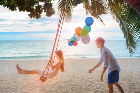 Paar Liebhaber im romantischen Honigkuchen am Strand sitzen auf dem Holzschaukel und lachen , um das Meer zu beobachten