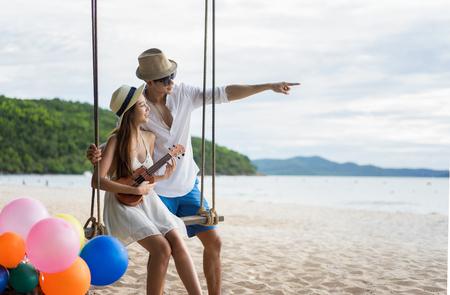 coppia amante nella romantica luna di miele sulla spiaggia seduta sull'altalena in legno gioiosa e guardando avanti verso il mare