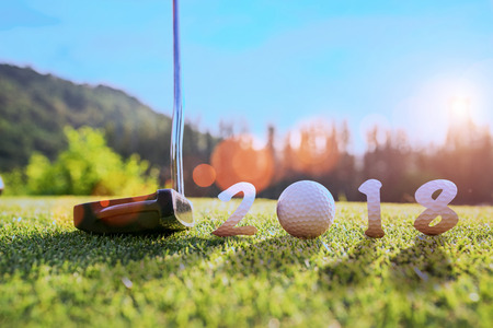 concept of golf ball invitation incomming year 2018, on the green prepare and ready to hit away by putter to the hole on the green in the golf course Stockfoto