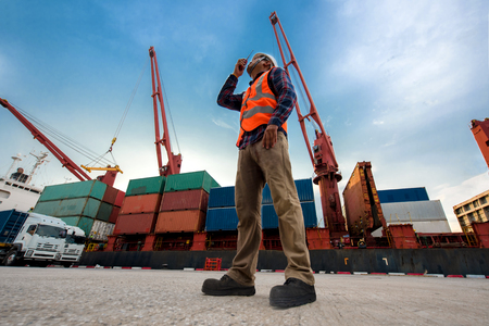 Foreman loading master takes control the operation in command working by radio walkie talkie in loading discharging the cargo container shipment at the ship in the porrt terminal Stock Photo