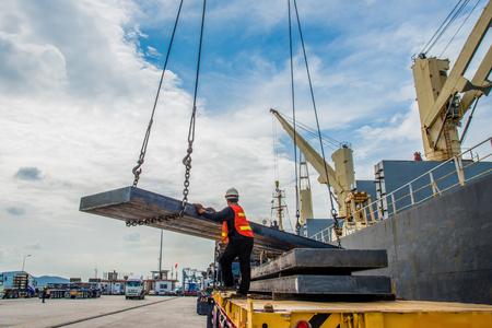 Lading stalen plaat lossen van het schip vaartuig tot op de vrachtwagen trailer rij op rij, de zending export en import onder logistieke systeemdiensten naar wereldwijde wereldwijde transport