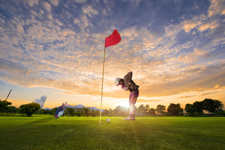 golf player in an attention putting a golf ball to hole on the green in a golf course at morning sunrise Stock Photo