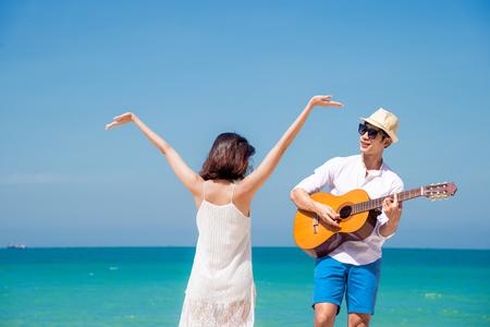 カップルの恋人は、歌や歌のギターを演奏して幸せをお楽しみください、記念日の新婚旅行、バレンタインの機会を祝って海のビーチで一緒に踊り