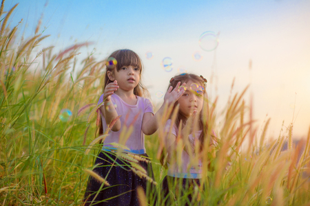 kids girls running around to pat plop of bubble in the air in fields of meadow at sunset