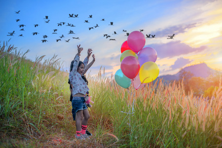 kids playing joyfull in the meadow on the hills with cheerfully in multicolor ballons, flock of bird flying over medow in background Stock Photo
