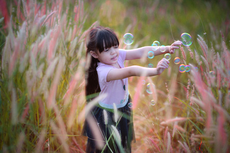 little girl scare of the bubble floating in the air, girl playing bubble on meadow of hill Stock Photo