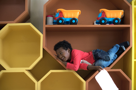 a  naughty preschool boy playing around in the slot pigeonhole box in classroom Stockfoto