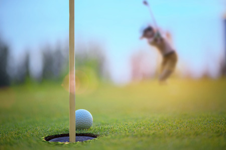 golf ball atmost on the edge of the hole on the green by golf player hit the ball from apron green to the hole Stok Fotoğraf