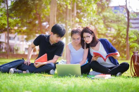 Joven estudiante asiática disfruta compartiendo el conocimiento y la tutoría del tema juntos después de la clase en el parque de la universidad Foto de archivo - 93328019
