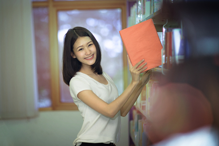 student doing project in library of University, takes subject book on the  bookshelf with a cute smile