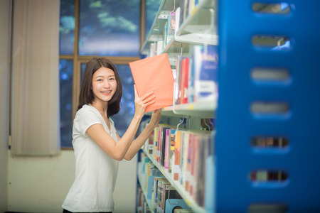 student holding books from bookshelf of library of University for doing a project submit in time