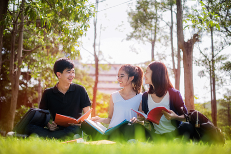 young asian student enjoy sharing knowledge and tutoring of subject together after class in park of university Stock Photo