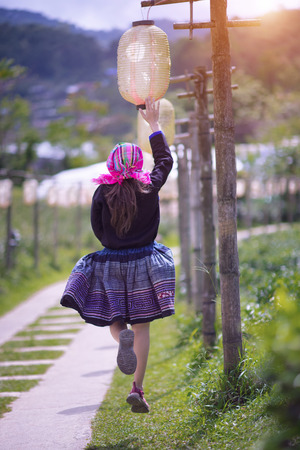 local village woman running and jumping in walk way touching lantern lamp, happy and enjoy easy life in countryside Stock Photo