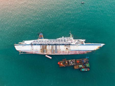 싱크대 여객선이 바다 한가운데에서 오염을 제거하기 위해 고철, 쓸모없고 잔해 정크 선박을 자르고 누워 있습니다.