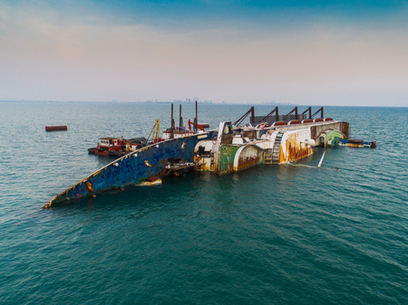 A sink passenger ship lie down in middle of the sea under cutting scrap iron, useless and wreckage junk ship for rid of destroy away from pollution
