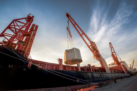Heavy lift ship handle heavy shipment package by ship crane at under control in safety working loading at all time Stock Photo