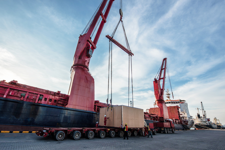 heavy lift cargo handle by the professional teamwork to locate the package from the ship crane onto the center gravity of the lowbase trailer to make sure safety balance carry out in properly safe working.