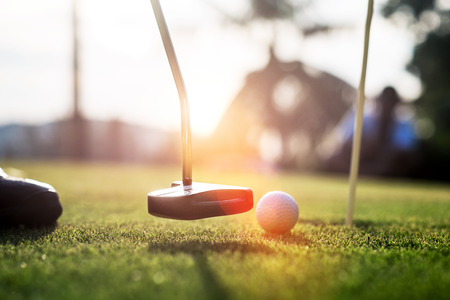 putter going to impact golf ball on the green to the hole by the player Stock Photo