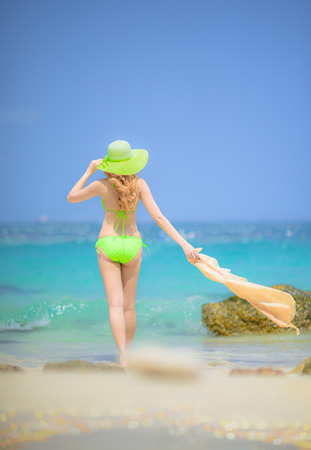 woman wearing bikini walking and enjoy summer on the beach of island, with blue sky and cleared water in background