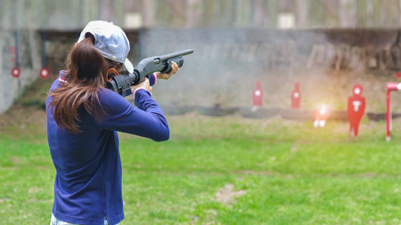 woman in practice shooting gun riffle in martial arts for self defense in an emergency case Stock Photo