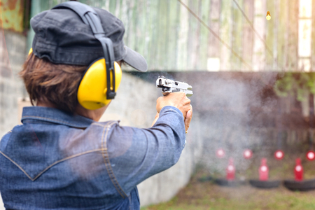 shot gun magazine in hand of old woman is reflect in flicking after shooting bullet away to the target, effective against weight of gun recoil spring works after shooting by stable action Stock Photo