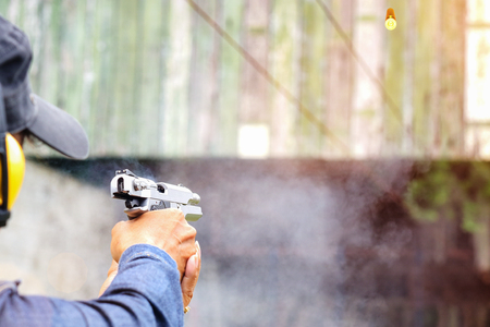 closeup of shot gun magazine in hand of old woman is reflect in flicking after shooting bullet away to the target, effective against weight of gun recoil spring works after shooting by stable action Stock Photo