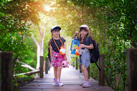 twin kids walking-in wooden bridge of forest jungle for joining field trip for replenish nature life education, looking to see at dark forward find firerfly bug in the night with lamp lantern