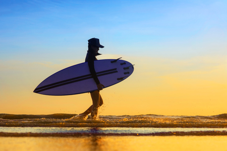 Silhouette of woman holding surfboard beside walking on the edge of sea wave, splash of water kicking while walking through, returning home stattion after surfed in the sea at sunset light Stock Photo