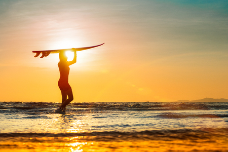 Silhouette of woman holding surfboard turn on the head walking on the edge of sea wave, retuning to home station after surfed in the sea at sunset light