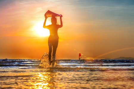 Silhouette of woman holding surfboard turn on the head walking on the edge of sea wave, splash of water kicking while walking through