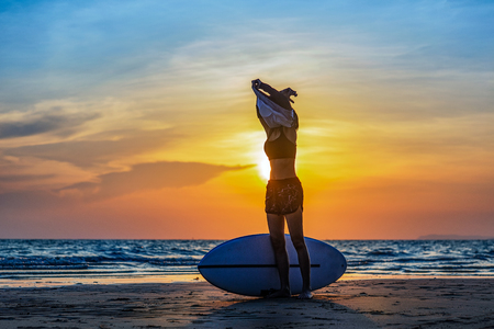 surfboard woman takes off sport shirt to practice water sport exercise at the sea