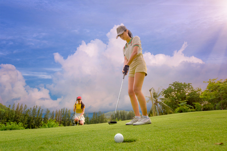 Young woman putting golf ball flow through the hole most successfully to the winner, golfmate competitor deactive looking forward in background