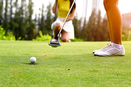 Golf ball run through the hole most successfully on the green, putting by woman golf player with golfmate competitor looks exciting in background Stock Photo