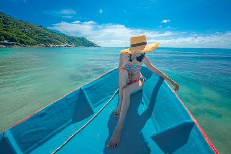 Slim woman relax and enjoy the sea by lie sitting down on the the prow of the local ferry boat bow, in holiday and long weekend vacation traveling in summer time