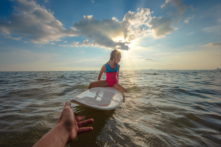 girl is obstinacy and conviction in refused or decline a hand help to support playing surfboard in sea water Stock Photo