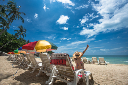 tourist woman cheerfully enjoy with the beach nature on the island by laying sitting on the deck couch beach with blue clear sky, summer time and vacation holidays occasion